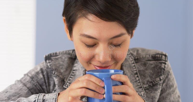 Riechender Tasse Kaffee der netten Asiatin lizenzfreie stockfotos