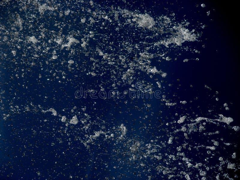 Riegue, chapoteo del agua aislado en fondo azul foto de archivo