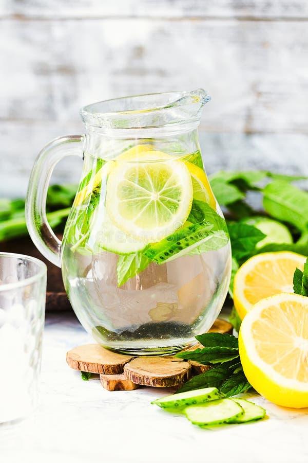 Riegue con el limón, la menta y el pepino en el vidrio, fondo ligero imagen de archivo