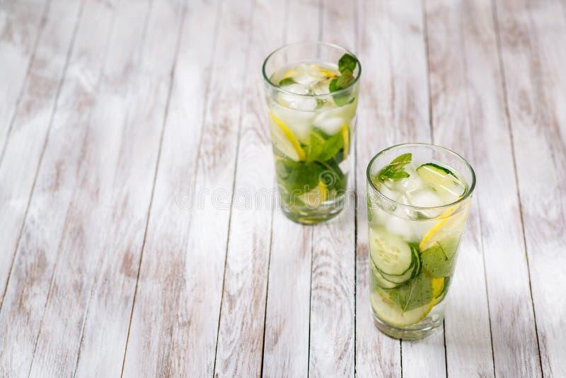 Riegue con el limón, la menta y el pepino en fondo ligero de madera Detox del agua imagenes de archivo