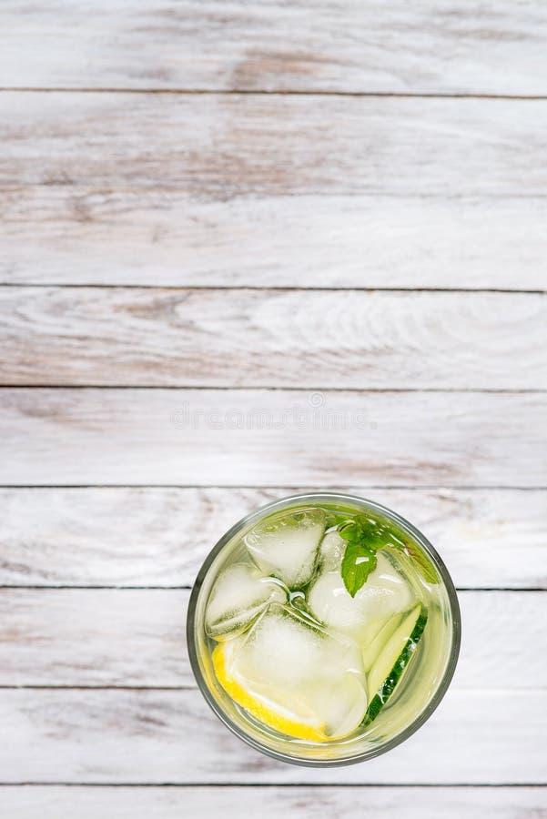Riegue con el limón, la menta y el pepino en fondo ligero de madera Detox del agua Visión superior fotos de archivo
