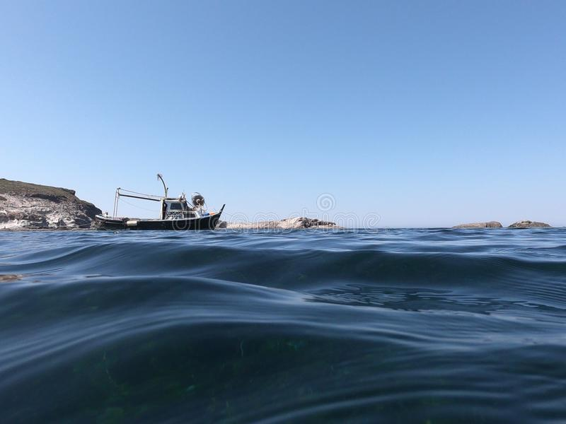 Riegue el borde con la opinión del barco y el mar azul fotografía de archivo