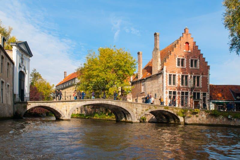 Riegue el canal con el puente viejo y las casas medievales en Begijnhof, Brujas, Bélgica imagenes de archivo