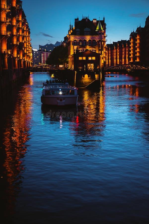 Riegue el castillo en Speicherstadt viejo o almacene el distrito, barco turístico en un canal Hamburgo, Alemania imagen de archivo libre de regalías