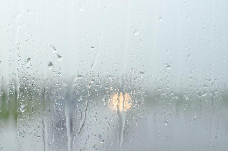 Riegue el descenso, gota de lluvia sobre el vidrio y el goteo abajo fotografía de archivo