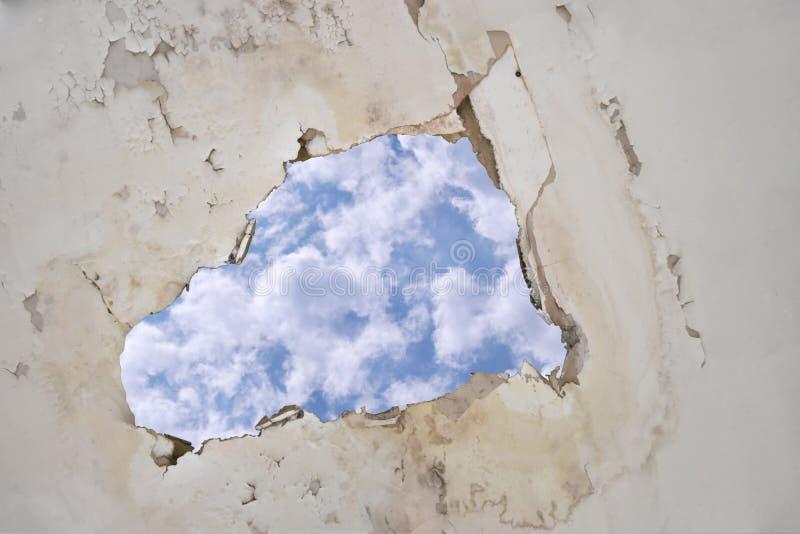 Riegue el escape en el techo que causa las tejas del daño, cielo fotografía de archivo libre de regalías