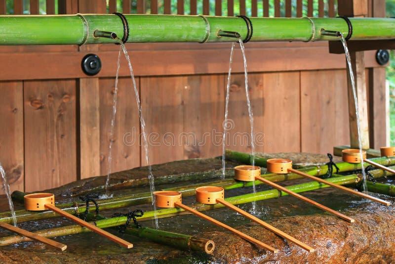 Riegue el funcionamiento hacia fuera a través del tubo de bambú para regar el lavabo en Shimogam imágenes de archivo libres de regalías