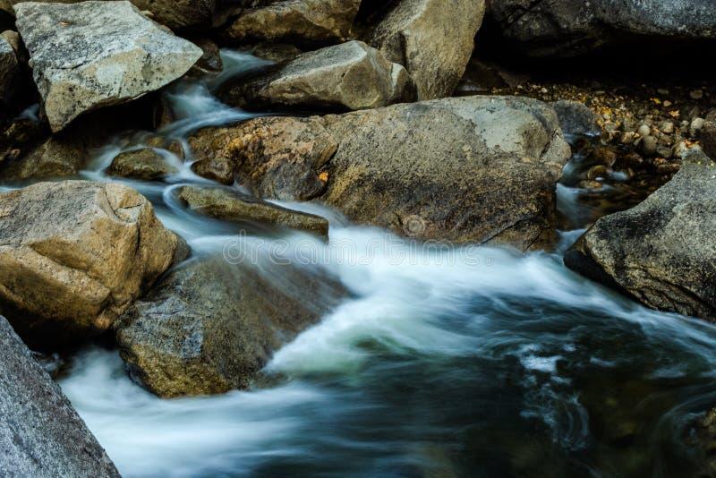 Riegue fluir sobre rocas y rio abajo de Merced en la oscuridad fotografía de archivo libre de regalías
