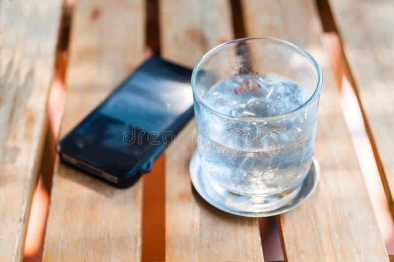 Riegue la bebida en vidrio con el teléfono en la tabla de madera fotografía de archivo libre de regalías