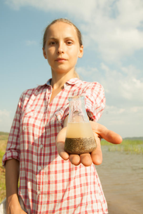 Riegue a la mujer de la prueba de la pureza que sostiene el frasco químico con agua, el lago o el río en el fondo fotos de archivo libres de regalías