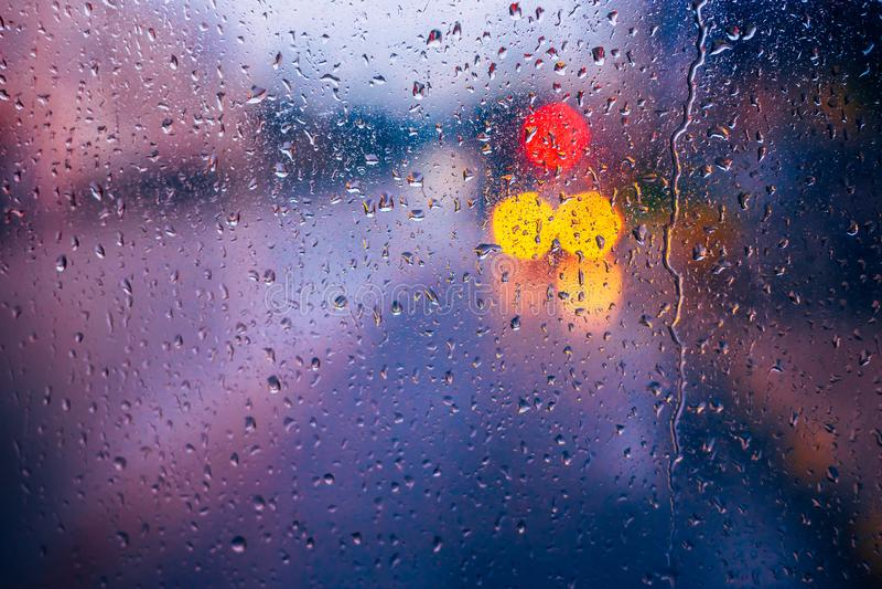 Riegue las gotas de la lluvia en fondo de cristal azul Luces de Bokeh de la calle fotos de archivo libres de regalías