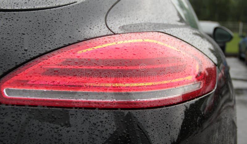 Riegue los descensos en luces posteriores del coche después de fotos antis de la acción de la capa de la protección de lluvia fotografía de archivo