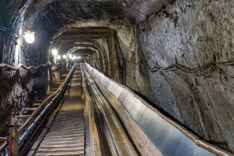 Riem conveyot in verlichte ondergrondse tunnel royalty-vrije stock afbeeldingen