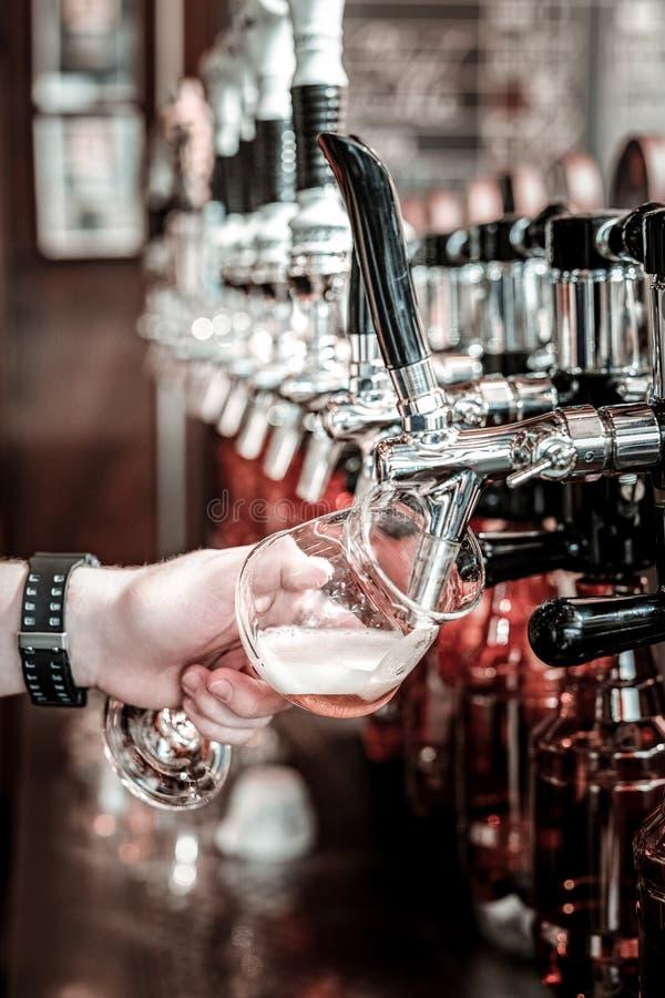 Riempiendo il vetro di lager dal rubinetto della birra immagine stock