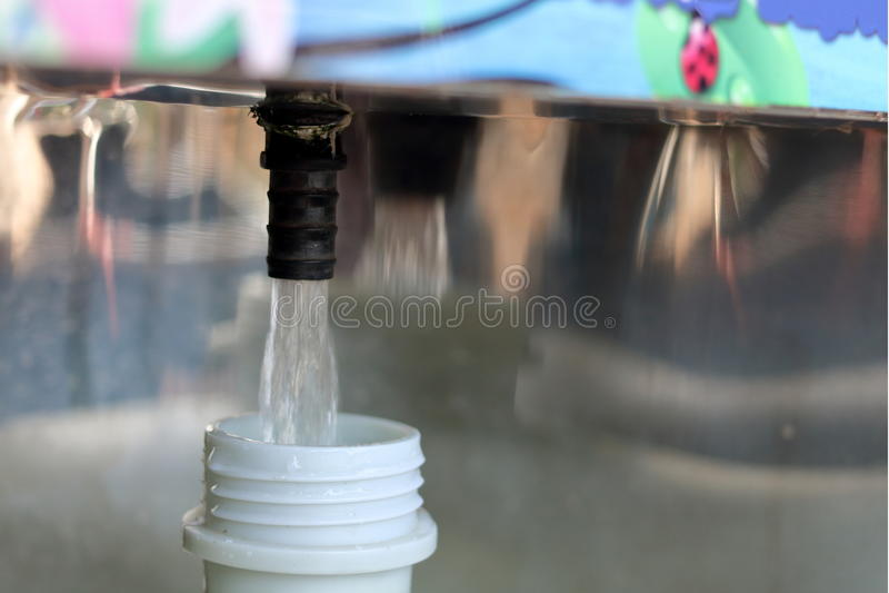 Riempimento della bottiglia di acqua di plastica da un distributore automatico, profondità di campo bassa immagini stock