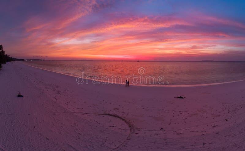 A?rien : ciel de observation de coucher du soleil de couples se reposant sur le ciel romantique de plage de sable au coucher du s images libres de droits