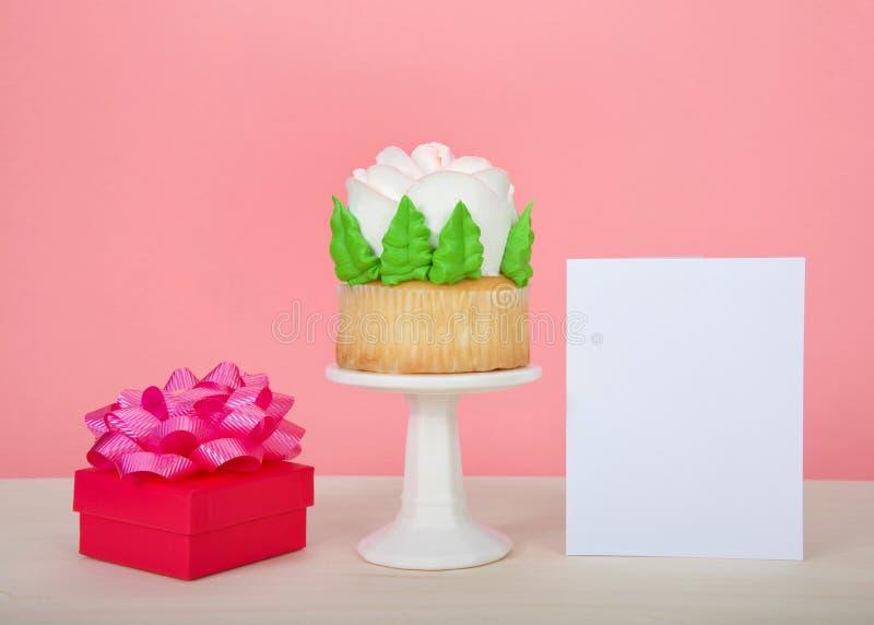 Riese stieg kleiner Kuchen auf Sockel mit anwesender und leerer Karte lizenzfreie stockbilder