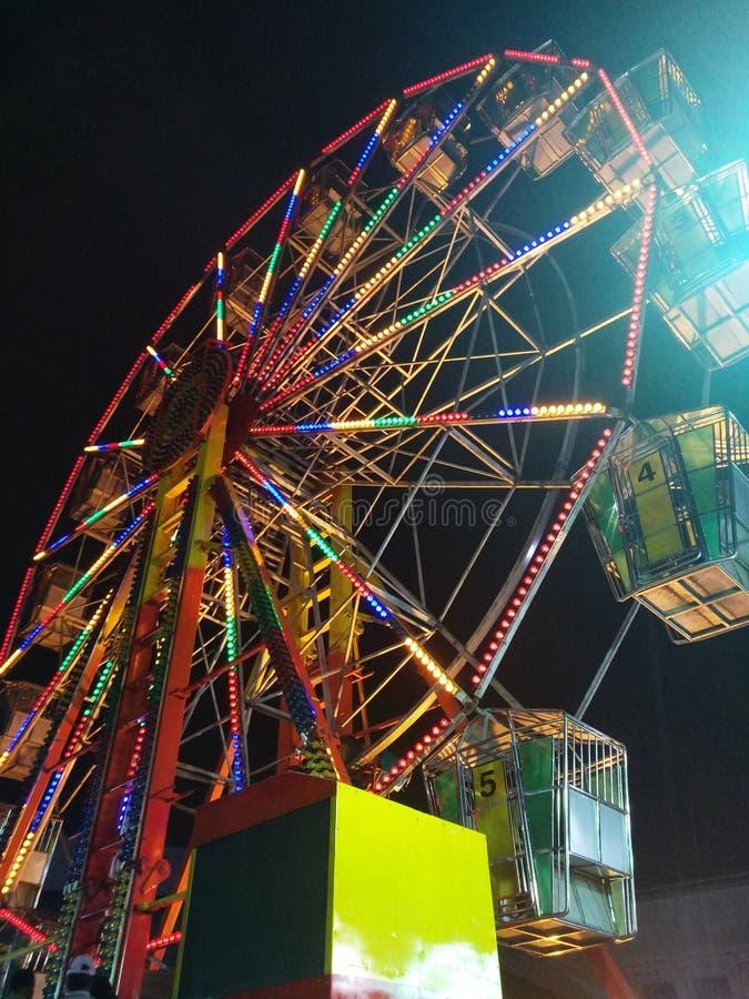 Riesenrad an einer FunfairVergnügungsparkfahrt stockbild