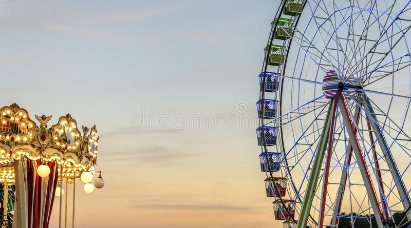 Riesenrad herein einen Rummelplatzpark nahe bei einem Karussell lizenzfreies stockbild
