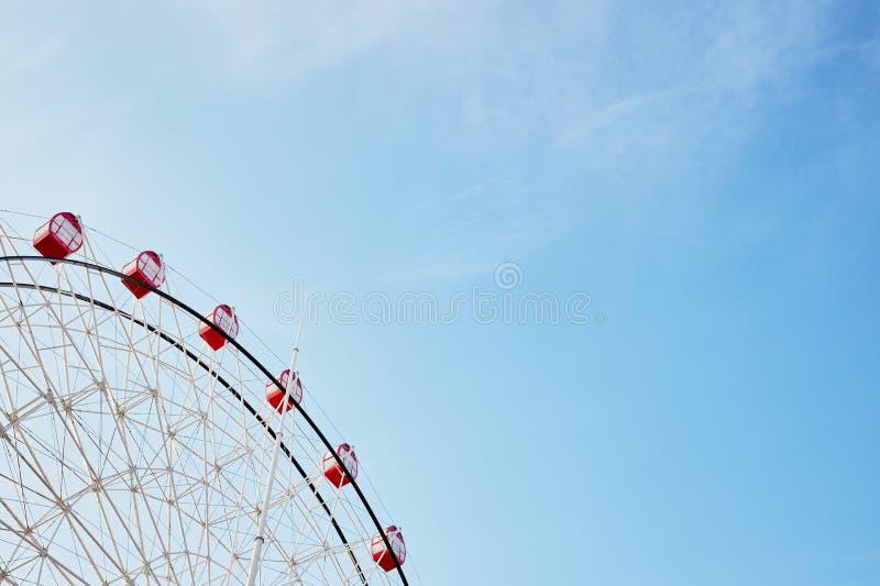Riesenrad mit leuchtend roten Ständen auf dem Hintergrund des ruhigen klaren blauen Himmels als Symbol für Freude Erholung Spaß u lizenzfreie stockfotografie