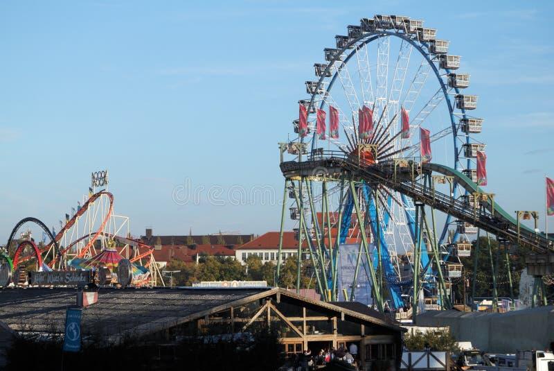 Riesenrad und Achterbahn beim Oktoberfest stockbild