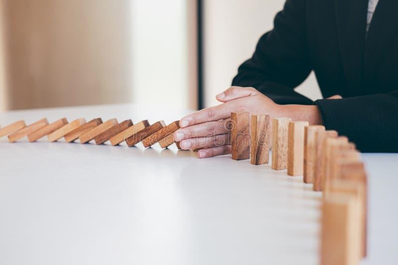 Riesgo y estrategia en el negocio, imagen de la mano que para efecto de dominós de madera descendente del bloque del hundimiento  imágenes de archivo libres de regalías