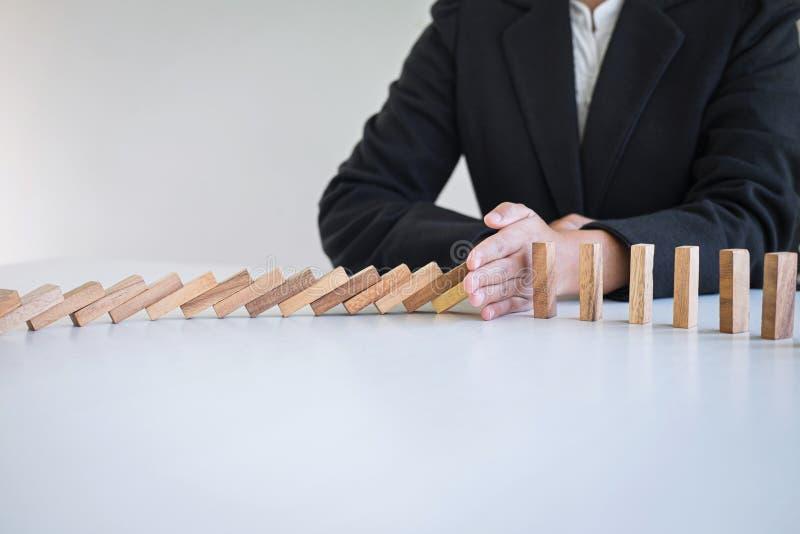 Riesgo y estrategia en el negocio, imagen de la mano que para efecto de dominós de madera descendente del bloque del hundimiento  imagen de archivo