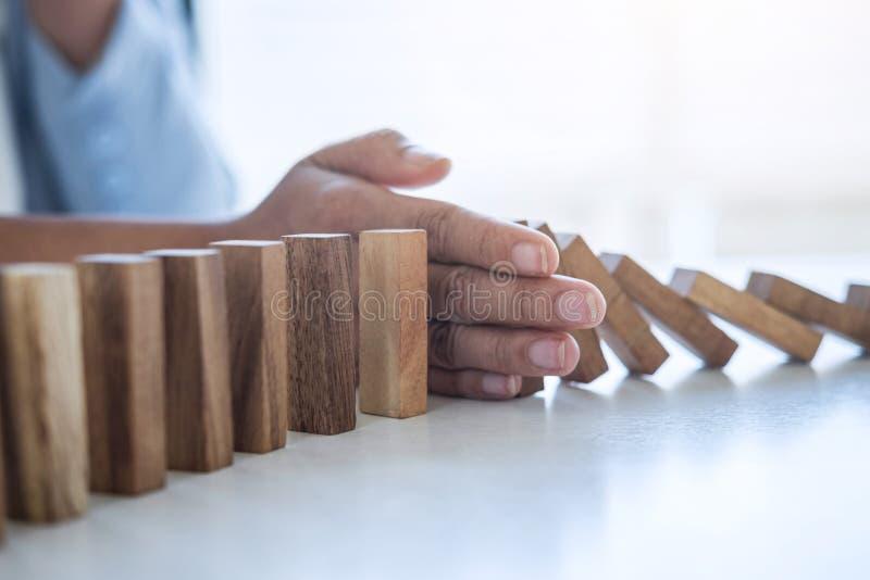 Riesgo y estrategia en el negocio, imagen de la mano que para efecto de dominós de madera descendente del bloque del hundimiento  foto de archivo