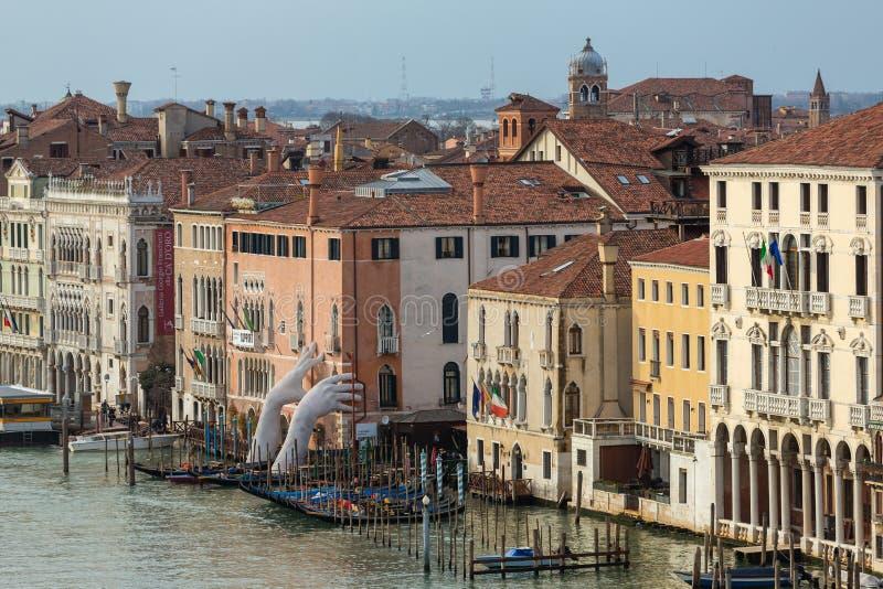 Riesige Hände steigen vom Wasser von Grand Canal, um das Gebäude in Venedig zu stützen stockfotos