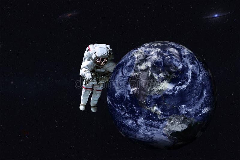 Riesiger Astronaut nahe Erdplaneten des Sonnensystems lizenzfreies stockfoto