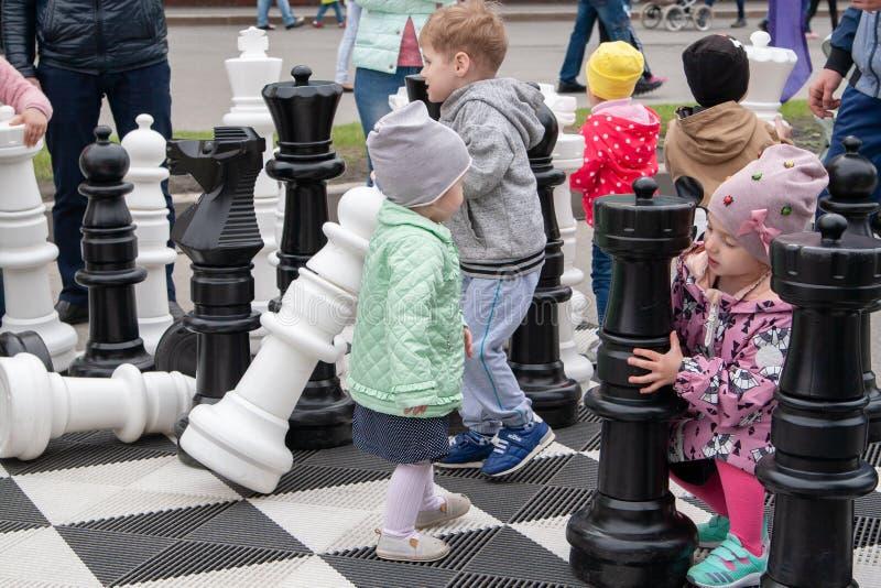 Riesiges Schach Kinder auf dem Schachbrett, unter den riesigen Schachfiguren stockfoto