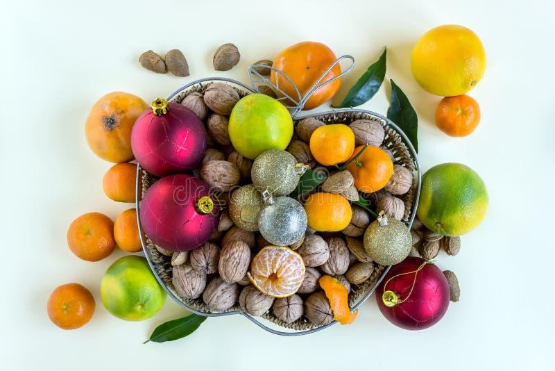 Rieten die mand met noten, mandarijnen en dadelpruimen wordt gevuld De feestelijke stemming wordt gecreeerd door rode en zilveren stock foto's