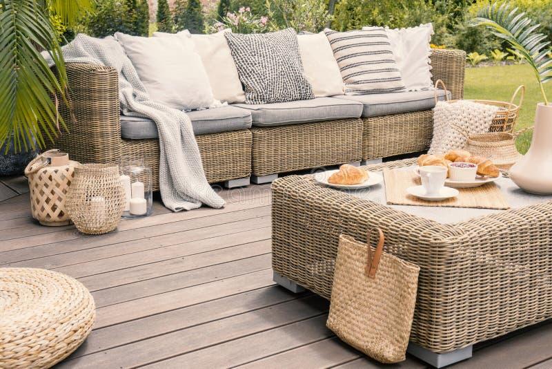 Rieten die terras met beige kussens wordt geplaatst die zich op een houten raad bevinden royalty-vrije stock fotografie