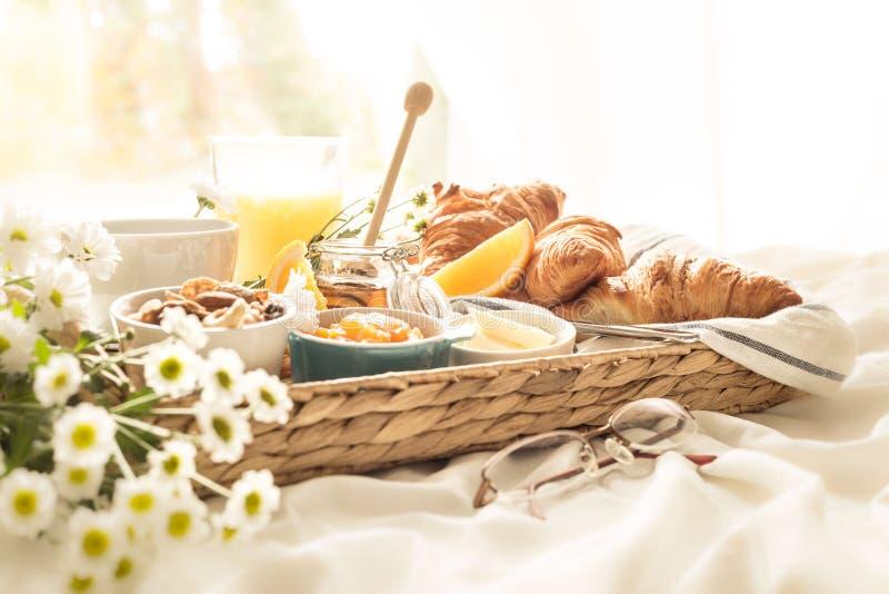 Rieten dienblad met continentaal ontbijt op witte bedbladen royalty-vrije stock afbeeldingen