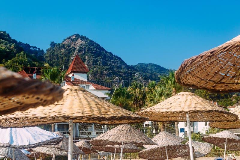 Rieten grote paraplu's op sunbeds op het strand van het hotel royalty-vrije stock afbeeldingen