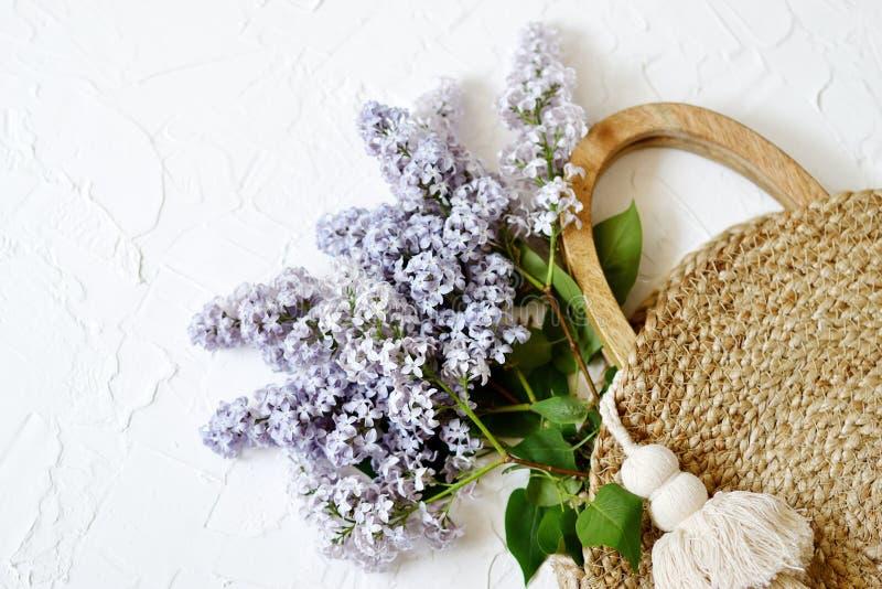 Rieten Handtas met Lilac Bloemen, de Lentetijd, de Zomerconcept royalty-vrije stock afbeelding