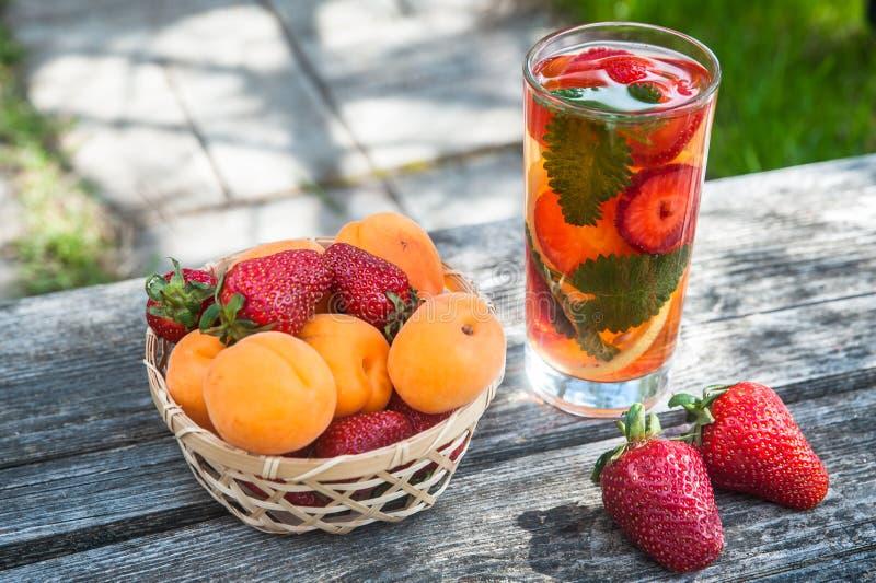 Rieten mand met aardbeien en abrikozen, hoogste mening, glaswi royalty-vrije stock afbeeldingen