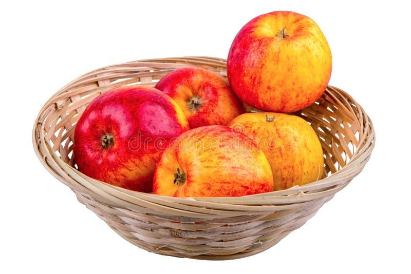 Rieten mand met appelen op een witte achtergrond stock foto