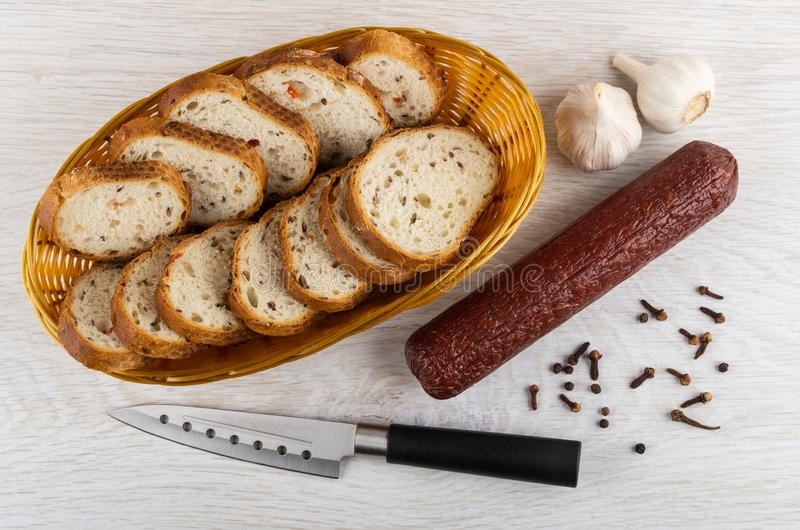 Rieten mand met brood, gerookte worst, knoflook, zwarte peper, kruidnagelkruid, mes op lijst Hoogste mening stock foto