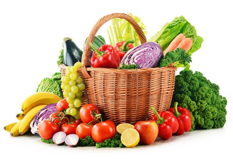 Rieten mand met geassorteerde organische groenten en vruchten stock afbeeldingen