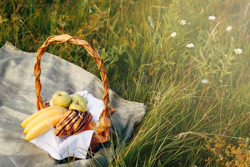 Rieten mand op groen gras, picknick in het Park buiten op de zomerdag stock foto's