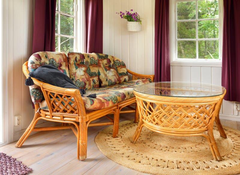 Rieten meubilair in loge stock afbeeldingen
