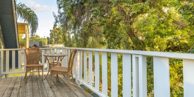 Rieten meubilair op balkon die weelderige bomen overzien stock foto