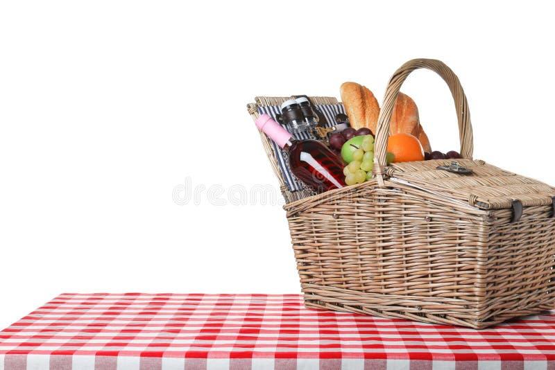 Rieten picknickmand met verschillende producten op geruit tafelkleed tegen witte achtergrond stock fotografie