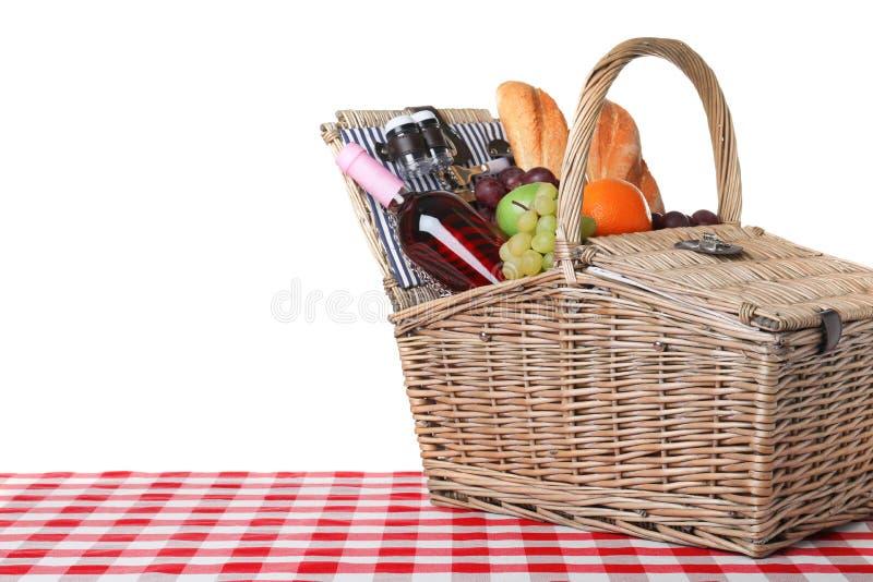 Rieten picknickmand met verschillende producten op geruit tafelkleed tegen witte achtergrond, ruimte voor royalty-vrije stock foto