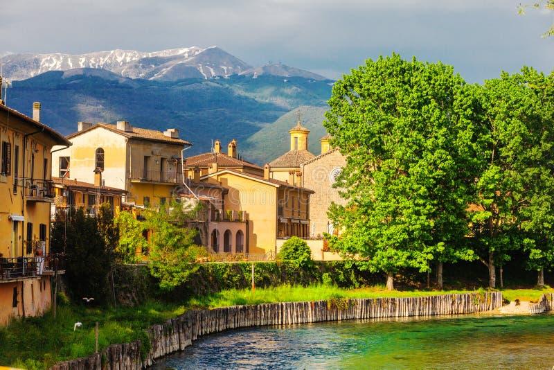Rieti stad av centrala Italien Fiume Velino med forntida hus och det Terminillo berget upptill royaltyfri foto