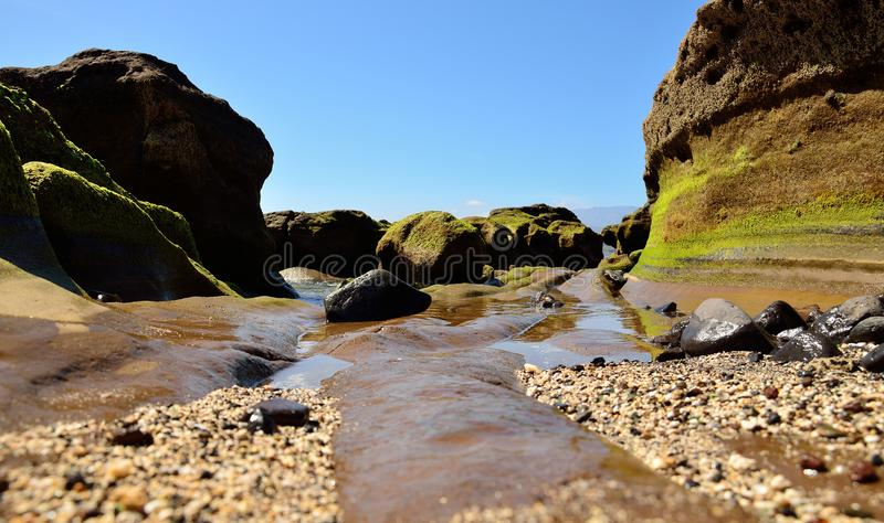 Riff bei Ebbe und blauer Himmel lizenzfreie stockbilder