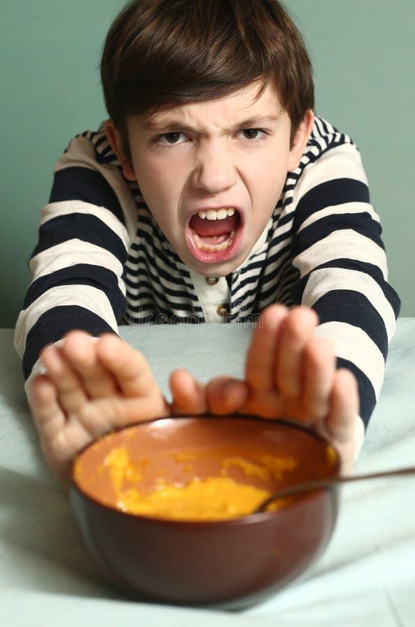 Rifiuti del ragazzo dal cibo della minestra fracassata della zucca immagine stock