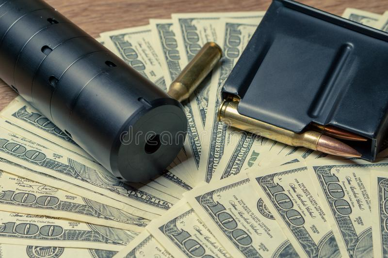 Rifle barrel, suppressor and cartridges on dollars. Concept for crime, contract killing, paid assassin, terrorism, war. Global arms trade, weapons sale royalty free stock photos