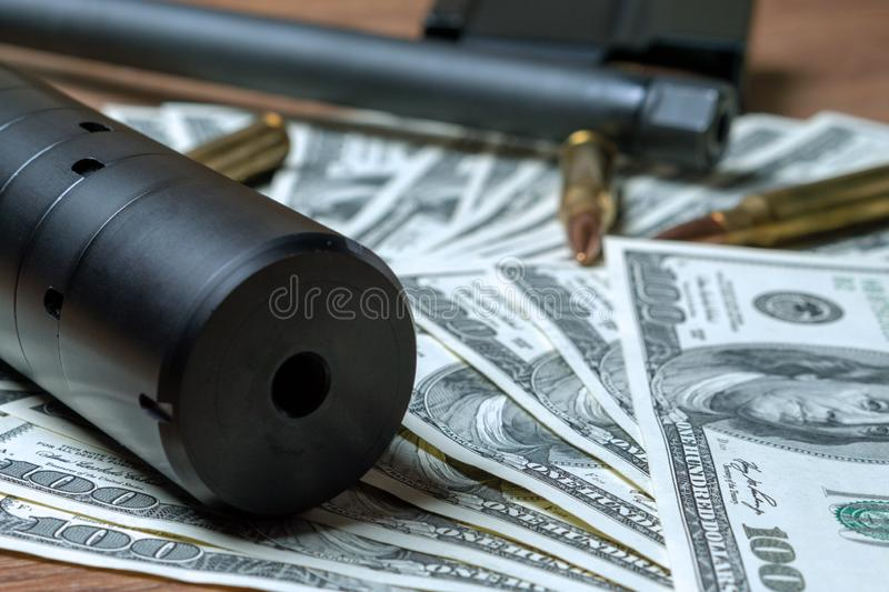 Rifle barrel, suppressor and cartridges on dollars royalty free stock photos